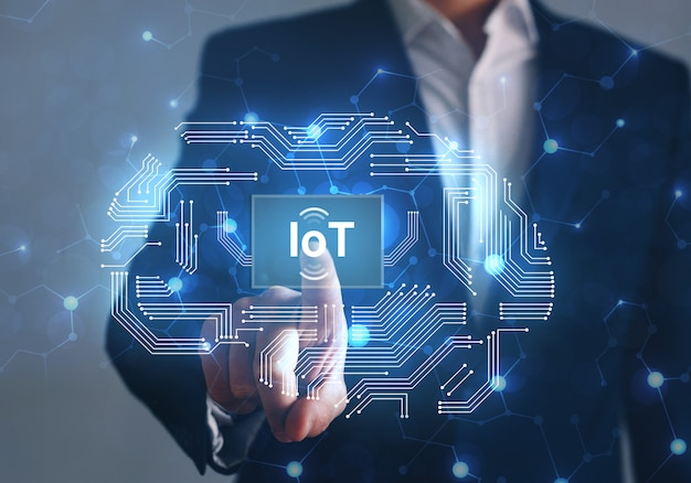 Biznesmen wskazując przycisk iot z abstrakcyjnymi urządzeniami chip. koncepcja internetu rzeczy.