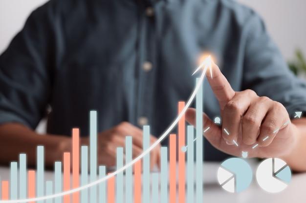 Biznesmen wskazuje palcem wykres strzałki plan rozwoju biznesu do sukcesu