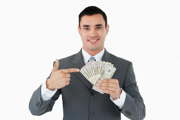 Biznesmen wskazuje przy banknotami w jego ręce
