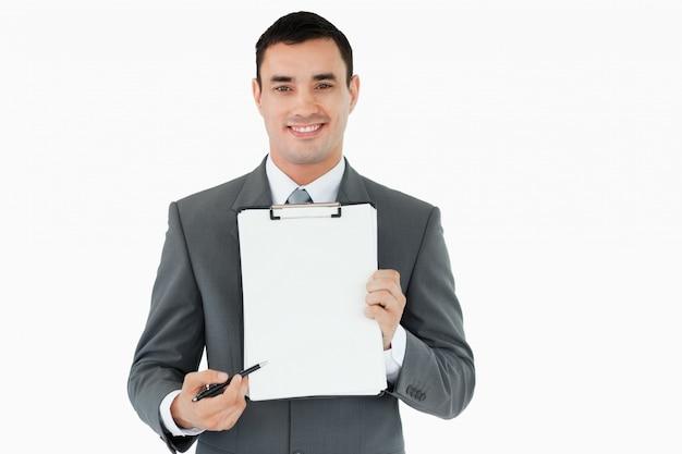 Biznesmen wskazuje z piórem na schowku