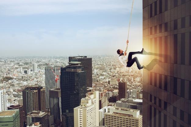 Biznesmen wspina się liną na wysoki budynek