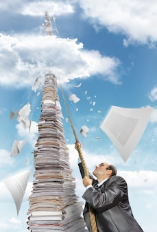 Biznesmen wspina się na stos dokumentów