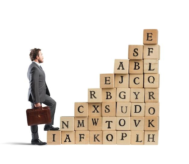 Biznesmen wspinać się po schodach kostki drewniane litery