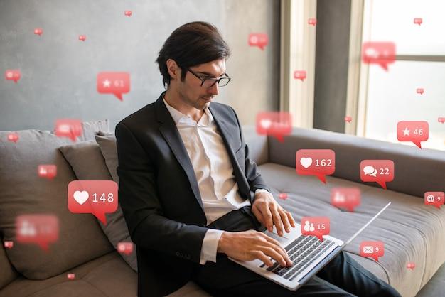 Biznesmen współpracuje z sieciami społecznościowymi i laptopem