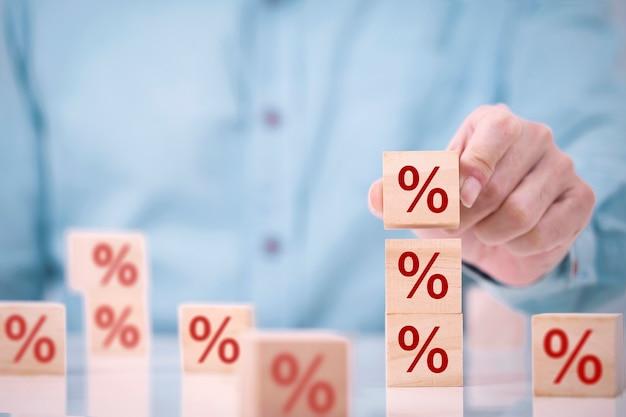Biznesmen wybiera drewniany blok kostki na górze z ikoną symbolu procentu, koncepcją finansów, oprocentowania i oprocentowania kredytów hipotecznych