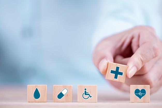Biznesmen wybiera emotikony ikony opieki zdrowotnej symbol medyczny na drewnianym bloku