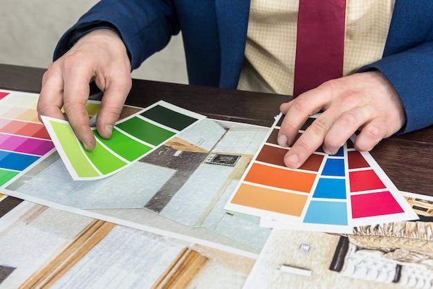 Biznesmen wybiera kolor swojego nowoczesnego mieszkania po remoncie. szkic domu z paletą kolorów
