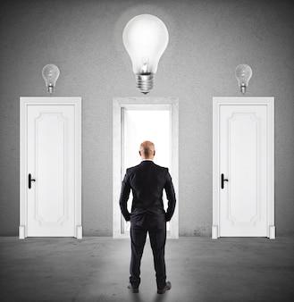 Biznesmen wybiera odpowiednie drzwi, w które wchodzi