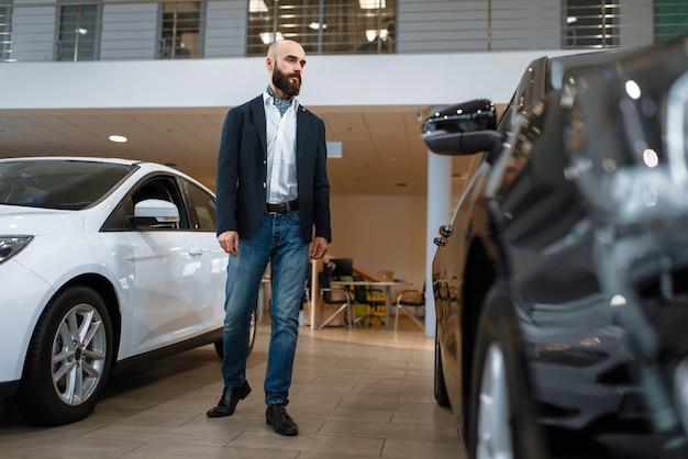 Biznesmen wybiera transport w salonie samochodowym. klient w salonie nowych pojazdów, mężczyzna kupujący samochód, dealer samochodowy
