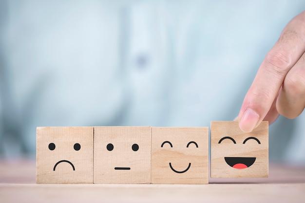 Biznesmen wybiera uśmiechniętą buźkę szczęśliwy symbol na drewnianym bloku