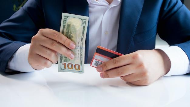Biznesmen wybierając między papierowymi banknotami i plastikową kartą redit.
