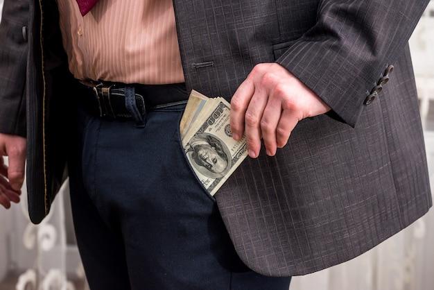 Biznesmen wyciągając pieniądze z kieszeni w spodniach