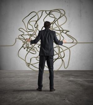Biznesmen wygląda mylić plątaninę liny. znajdź koncepcję rozwiązania