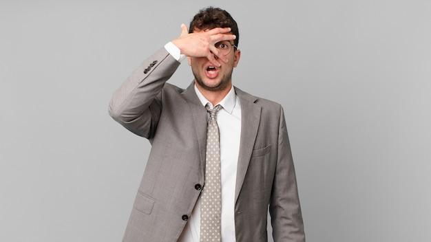 Biznesmen wyglądający na zszokowanego, przestraszonego lub przerażonego, zakrywający twarz dłonią i zerkający między palcami