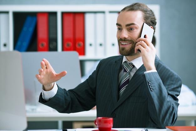 Biznesmen wyjaśnia klientowi szczegóły telefonu dotyczące transakcji