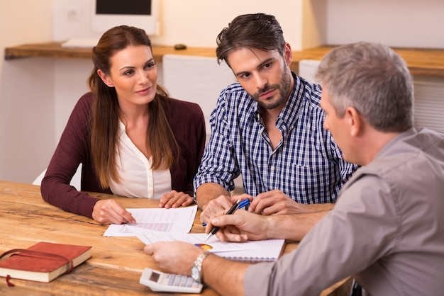 Biznesmen wyjaśniając politykę kredytową młodej parze. szczęśliwa młoda para omawia z agentem finansowym swoją nową inwestycję. doradca finansowy przedstawia młodej parze inwestycje bankowe.