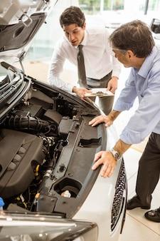 Biznesmen wyjaśniający szczegóły samochodu