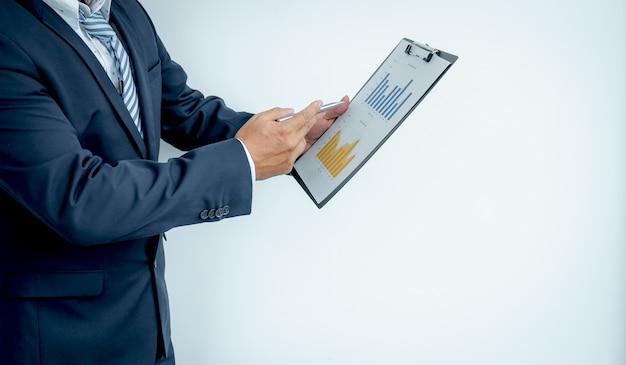 Biznesmen wykonawczej strony w garniturze trzyma pióro wskazujące na finansowy wykres.