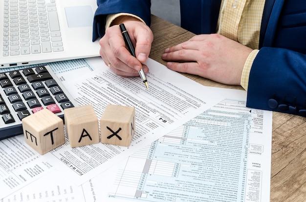 Biznesmen wypełniający formularz w-4 długopisem, kalkulatorem i komputerem