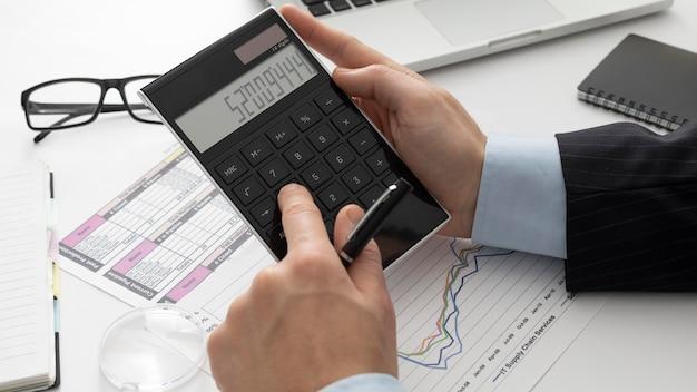 Biznesmen wysokiego kąta obliczania różnych liczb ekonomicznych