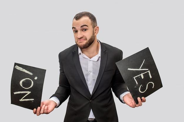 """Biznesmen ypung w garniturze posiada dwie czarne tabletki z napisanymi słowami """"tak"""" i """"nie"""". on patrzy w kamerę. facet ma wątpliwości."""