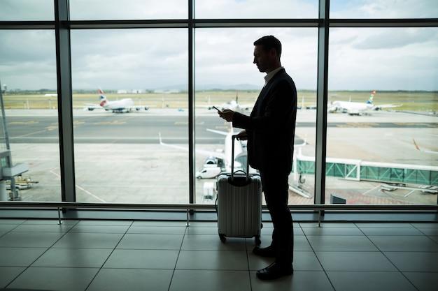 Biznesmen z bagażem za pomocą telefonu komórkowego