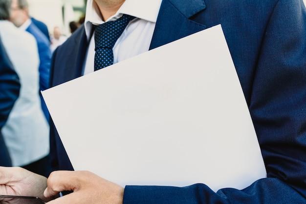 Biznesmen z białą falcówką i mobil telefonu kopii przestrzeni