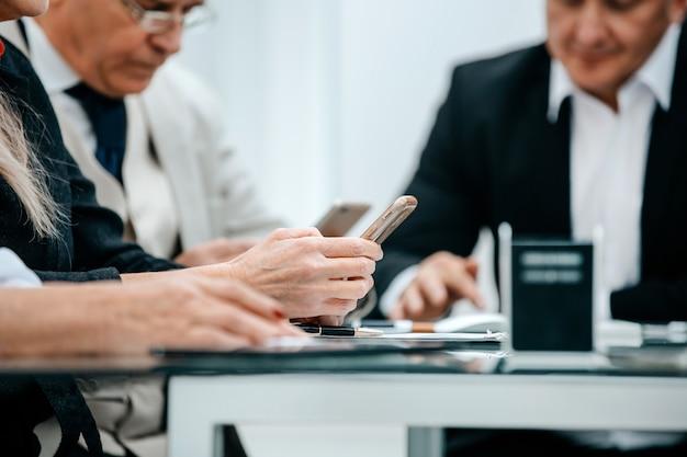 Biznesmen z bliska czyta sms na swoim smartfonie