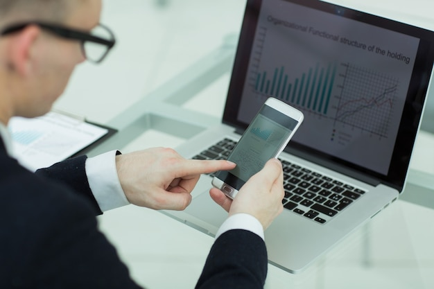 Biznesmen Z Bliska Używa Gadżetów Do Sprawdzania Danych Finansowych Premium Zdjęcia