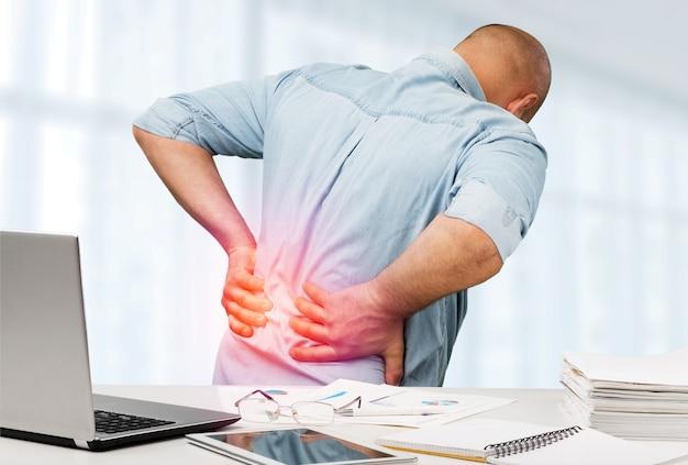 Biznesmen z bólem pleców biuro. koncepcja łagodzenia bólu