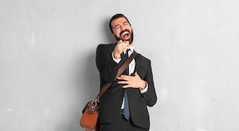 Biznesmen z brodą wskazując palcem na kogoś i śmiejąc się dużo