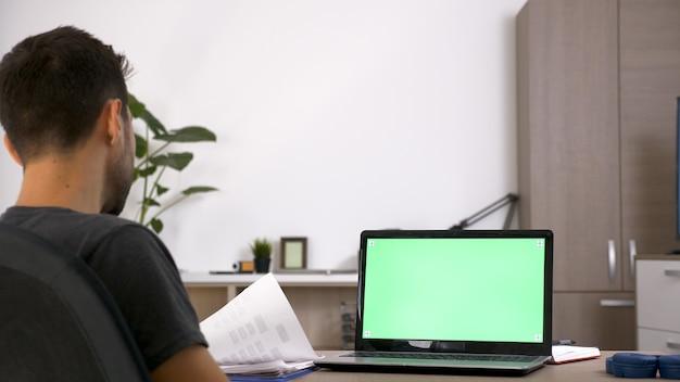 Biznesmen z brodą ciężko pracuje przy biurku w salonie swojego domu