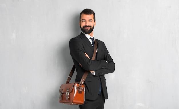 Biznesmen z brodą, trzymając ręce skrzyżowane w pozycji bocznej, jednocześnie uśmiechając się