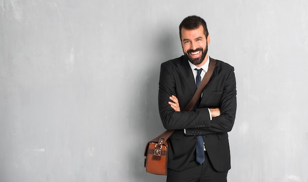 Biznesmen z brodą, trzymając się za ręce skrzyżowane, jednocześnie uśmiechając się