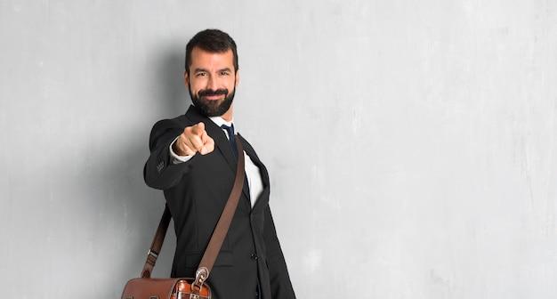 Biznesmen z brodą wskazuje palec z ufnym wyrażeniem