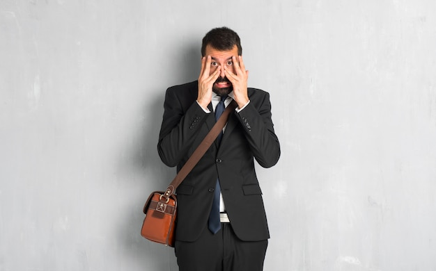 Biznesmen z brodą zaskakującą i zakrywa twarz z rękami podczas gdy patrzejący przez palców