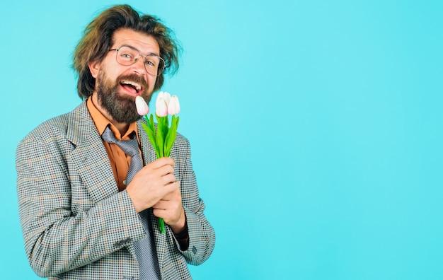 Biznesmen z bukietem tulipanów na urodziny. przystojny mężczyzna z kwiatami. uśmiechnięty mężczyzna z bukietem kwiatów. skopiuj miejsce.