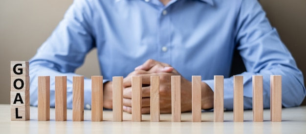 Biznesmen z celem drewniane bloki lub domino. biznes