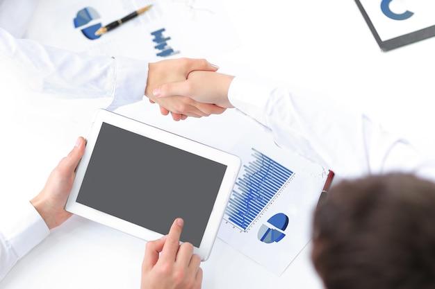 Biznesmen z cyfrowym tabletem i uścisk dłoni z partnerami finansowymi