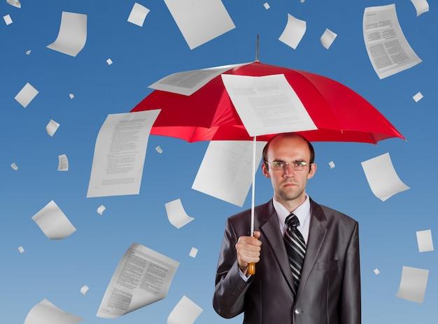 Biznesmen z czerwonym parasolem pod spadającymi dokumentami