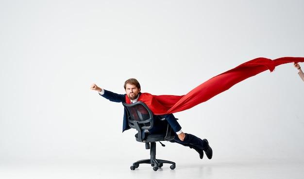 Biznesmen z czerwonym płaszczem próbuje w fotelu biurowym supermana