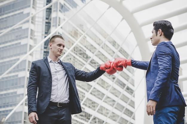 Biznesmen z czerwonymi bokserskimi rękawiczkami przygotowywać zwalczać jego coworker.