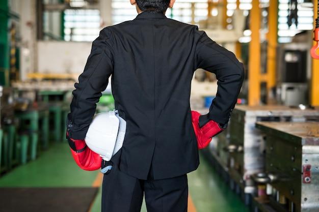Biznesmen z czerwonymi rękawiczkami i hełmem w fabryce