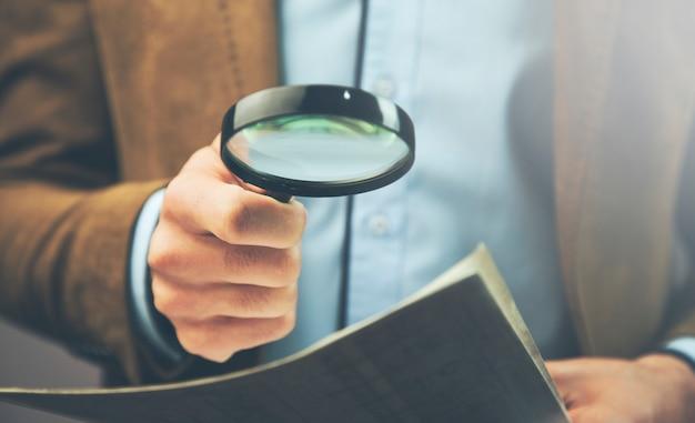 Biznesmen z dokumentem i magnifier w biurze