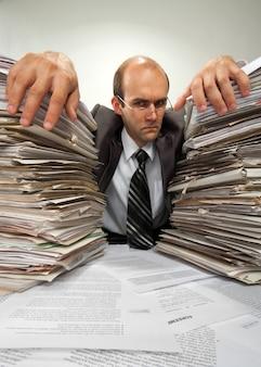 Biznesmen z dużymi stosami dokumentów