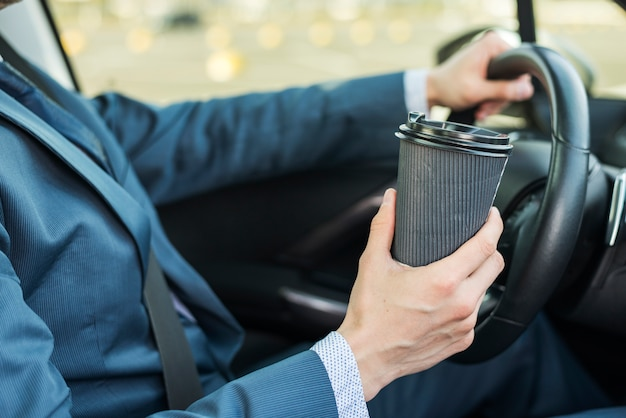 Biznesmen z filiżanką w samochodzie