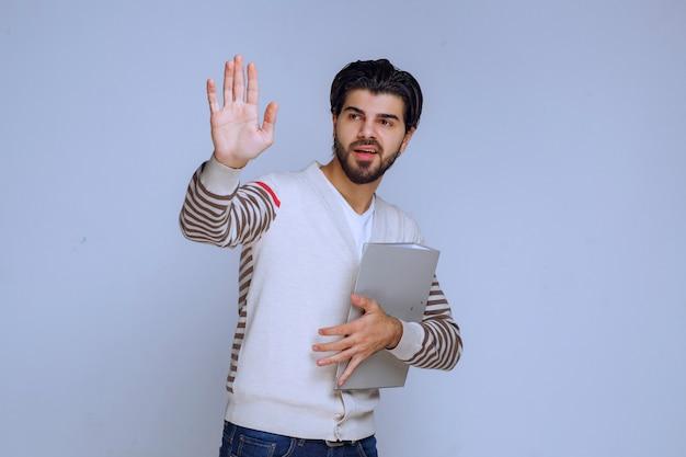 Biznesmen z folderem projektu, ściskając rękę i witając swoich kolegów.