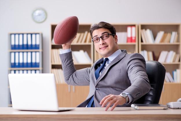 Biznesmen z futbolem amerykańskim w biurze