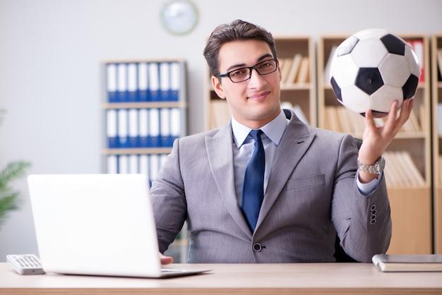 Biznesmen z futbolową piłką w biurze