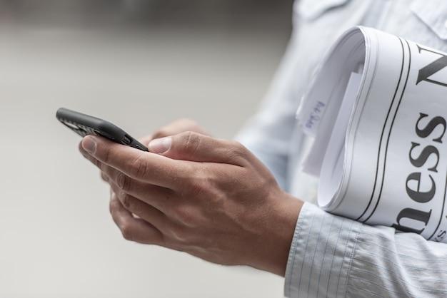 Biznesmen z gazetą używać smartphone szukać wiadomość dnia.